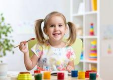 Kind, das zu Hause malen oder Kindertagesstätte stockfotografie