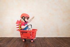 Kind, das zu Hause mit Spielzeugrakete spielt stockfotos