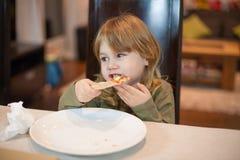 Kind, das zu Hause Pizza mit den Händen isst stockfotos