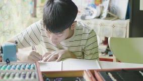 Kind, das zu Hause am Schreibtisch sitzt und seine Hausarbeit tut stock video footage