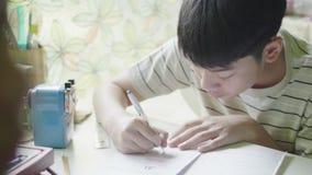 Kind, das zu Hause am Schreibtisch sitzt und seine Hausarbeit tut stock footage