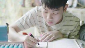 Kind, das zu Hause am Schreibtisch sitzt und seine Hausarbeit tut stock video