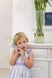 Kind, das zu Hause am Telefon spricht Lizenzfreies Stockfoto