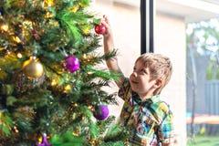 Kind, das zuhause Weihnachtsbaum verziert lizenzfreie stockfotografie