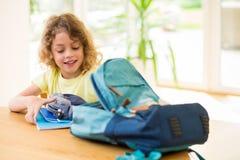 Kind, das zum shool sich vorbereitet und seine Tasche tut stockfotos