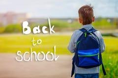 Kind, das zurück zur Schule mit Rucksack auf grünem Naturhintergrund mit Text zurück zu Schule geht Rückseitige Ansicht Lizenzfreie Stockfotos