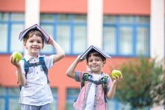 Kind, das zur Schule geht Der Junge und sein Freund, die B?cher auf Kopf halten, m?gen Hausdach am ersten Schultag stockbild