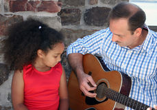 Kind dat aan gitaar luistert Stock Afbeeldingen