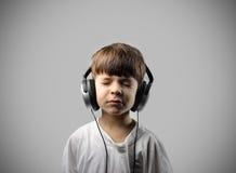 Kind dat aan muziek luistert Stock Foto's