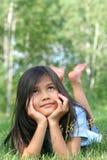 Kind dat bij gras het denken ligt royalty-vrije stock foto's