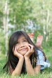 Kind dat bij gras het denken ligt stock foto