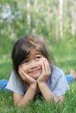 Kind dat bij gras het glimlachen ligt royalty-vrije stock afbeelding