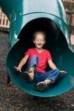 Kind dat bij speelplaats glijdt. stock foto's