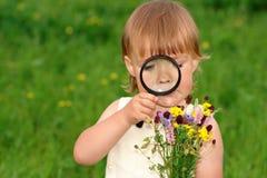 Kind dat bloemen door vergrootglas bekijkt royalty-vrije stock foto's