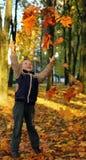 Kind dat de herfstbladeren werpt Royalty-vrije Stock Foto