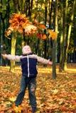 Kind dat de herfstbladeren werpt Stock Afbeelding