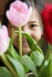 Kind dat door bloemen gluurt stock foto