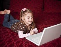 Kind dat een laptop computer met behulp van stock foto