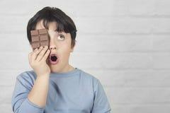 Kind dat een oog met een chocoladereep behandelt stock fotografie