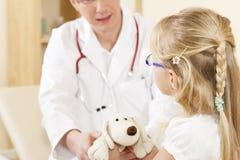 Kind dat een zacht stuk speelgoed geeft aan arts Royalty-vrije Stock Afbeeldingen