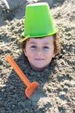 Kind dat in het zand wordt begraven royalty-vrije stock foto's