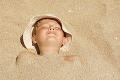 Kind dat in het zand wordt begraven stock foto's