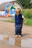 Kind dat kleine steen werpt aan pool Stock Afbeelding