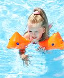 Kind dat met armbanden in zwembad speelt. Stock Foto