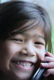 Kind dat op celtelefoon spreekt stock foto