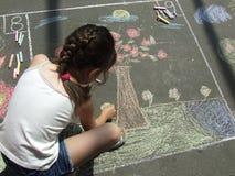 Kind dat op het asfalt w trekt Stock Foto's