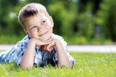 Kind dat op het gras ligt. Stock Fotografie