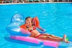 Kind dat op opblaasbare strandmatras zwemt Stock Afbeeldingen