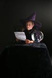 Kind dat in tovenaarskostuum zijn werktijd raadpleegt Stock Foto