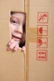 Kind dat van doos kijkt Stock Afbeeldingen
