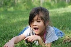 Kind dat voorwerp in gras vindt royalty-vrije stock fotografie