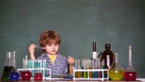 Kind in de klassenruimte met bord op achtergrond Chemieles De kleine verdienende chemie van de jonge geitjeswetenschapper binnen stock video