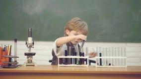 Kind in de klassenruimte met bord op achtergrond Laboratorium microscoop en het testen buizen Huis het scholen Mijn chemie stock video