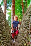 Kind in de pashindernis van de veiligheidsuitrusting in het park van de avonturenkabel stock foto's