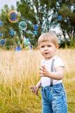 Kind in de zomer met zeepbels stock afbeeldingen