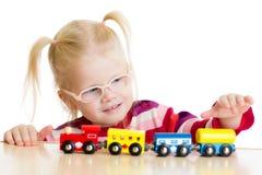 Kind in den eyeglases, die den Spielzeugzug lokalisiert spielen Lizenzfreie Stockfotos