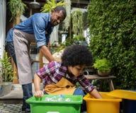Kind der afrikanischen Abstammung, das recyclebaren Abfall trennt stockfotografie