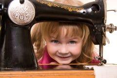 Kind an der alten Nähenmaschine Lizenzfreie Stockbilder