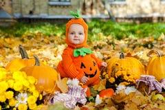 Kind in der Kürbisklage auf Hintergrund des Herbstlaubs Lizenzfreie Stockbilder