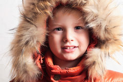Kind in der Pelzhaube und in der orange Winterjacke. Mode kid.children.close-up Lizenzfreie Stockbilder