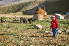 Kind in der roten Jacke in Kirgisistan Stockbilder