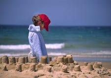 Kind in der roten Schutzkappe auf Strand Lizenzfreie Stockbilder
