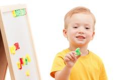 Kind an der Tafel mit Zahlen und Buchstaben bildet Wörter Stockfoto