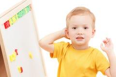 Kind an der Tafel mit Zahlen und Buchstaben bildet Wörter Lizenzfreies Stockbild
