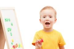 Kind an der Tafel mit Zahlen und Buchstaben bildet Wörter Stockfotografie
