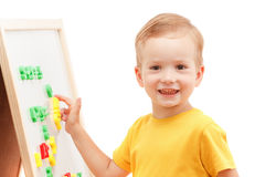 Kind an der Tafel mit Zahlen und Buchstaben bildet Wörter Stockbilder